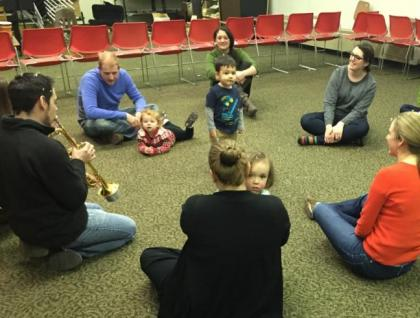 Small children and parents listening to music student playing.