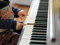 Young child at piano keyboard