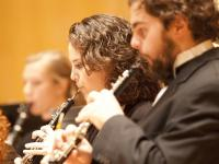Students playing the clarinet on stage.